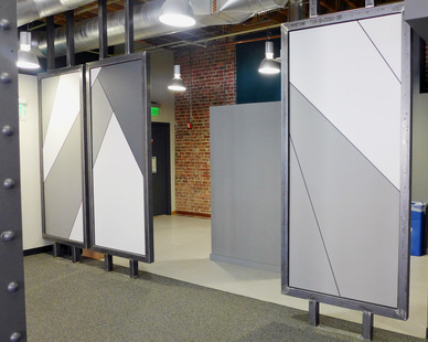 Custom floating metal panels with wood insets provide a stylish divider between work stations, by Jennifer Tulley Architects.