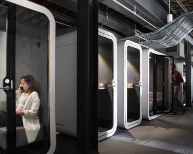 Modern office design featuring sound proof phone booths for phone calls.