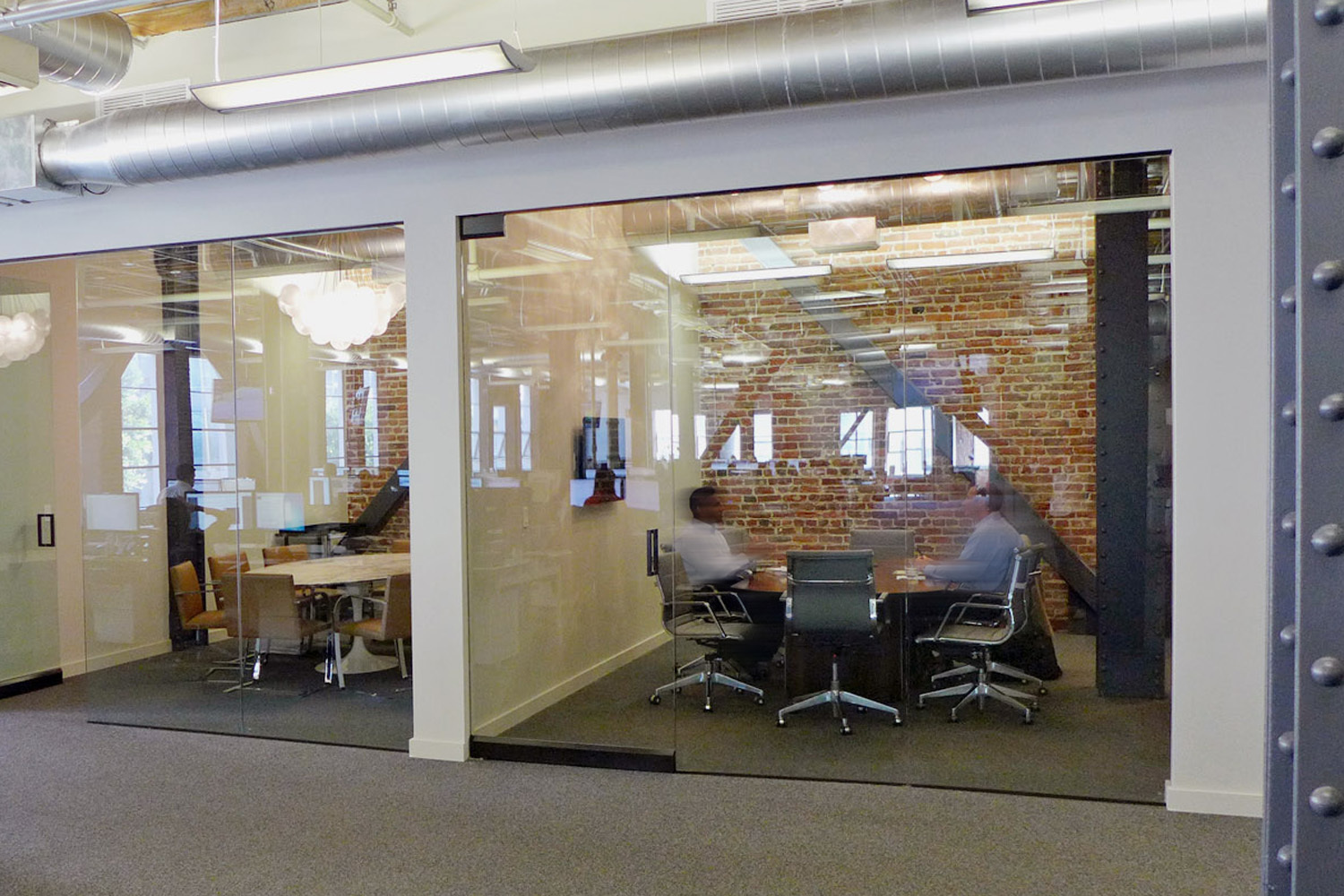 Exposed brick walls and glass paneling create an warm working environment, by Jennifer Tulley Architects.