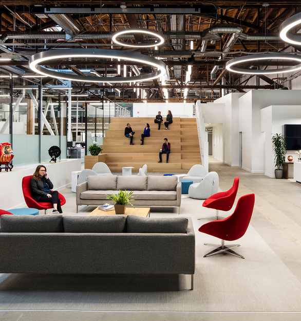 Santen Pharmaceutical Co., main entry lobby has a large stepped seating platform connected to an existing mezzanine to function as an all-hands meeting space, by Kava Massih Architects.