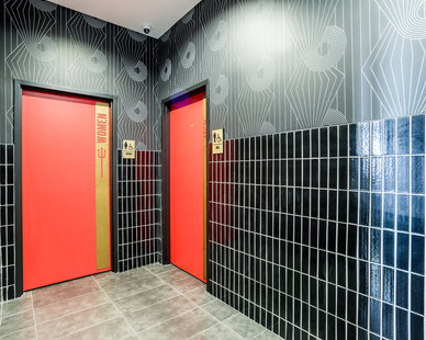 The restroom hallway walls incorporate various finishes and styles to continue the restaurant theme throughout the building.