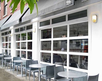 The fenestration of the front facade of HK Restaurant in New York, NY is to mimic the design of the garage doors. These doors fully open to the outside and along with the sidewalk tables give the feeling of alfresco dining in the summer.