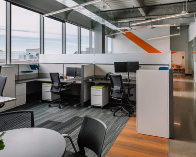 The exposed ceiling deck, angled LED light strips, low paneled workstations and full height glass create openness, encouraging natural light to permeate the space.