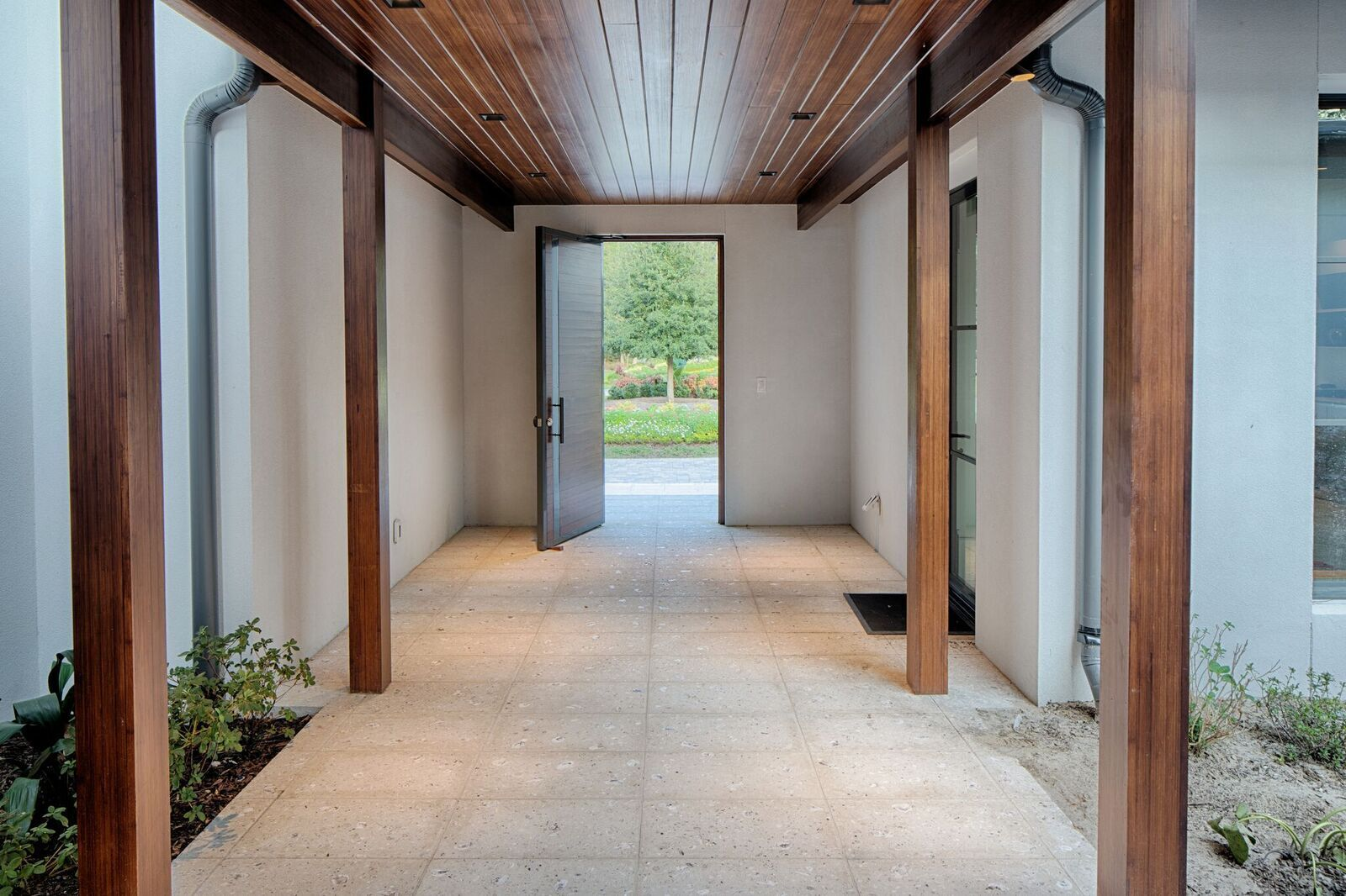 Seen here is the combination of Lamboo® Vue™ - Exterior Entry Door, Lamboo® Rainscreen™ - Soffit, & Lamboo® Structure™ - Posts & Beams on the exterior entryway of the home.