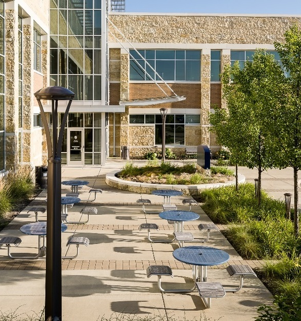 Exterior seating and tables at the Madison Area Technical College. Landscape Forms helped create a welcoming and pleasant atmosphere by incorporating lighting solutions from their Concord Collection.