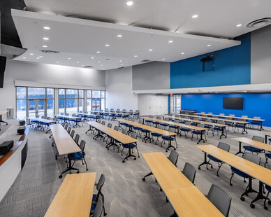 The auditorium space at SRF Consulting Offices is a perfect learning and meeting space for the employees.   This auditorium can fit over 100 people. The high ceilings, comfortable seating and blue accent walls make this space spacious and comfortable.