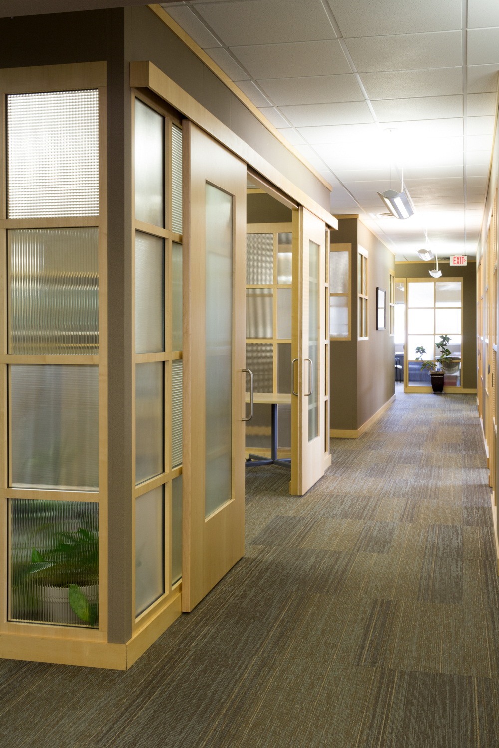 Textured glass walls let natural light flood into this hallway in the First Dakota Title office in Sioux Falls, South Dakota.