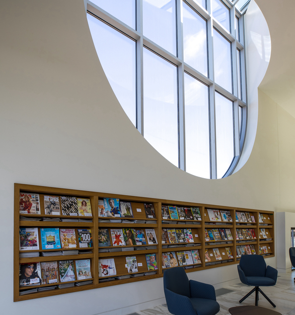 The arched window spans both floors of the library, providing light to the space. There are also comfortable seats for guests to stop and read.