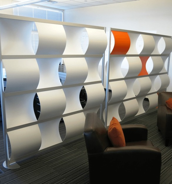 The design of the Wavewall by Loftwall functions as a filter between spaces. Wave's curved panel shape dampens sound and redirects ambient light to pass through the screens openings.
