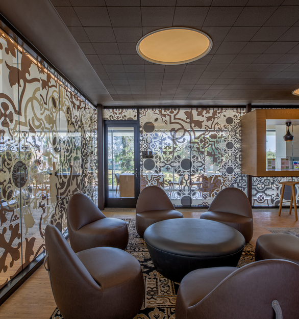 The cozy reading chairs and meeting area is encompassed by custom decorative graphic glass. The glass wall panels provide privacy and decoration to the space.