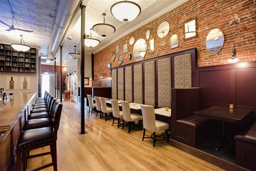 The main bar and seating area in a new, speakeasy-style wine bar.