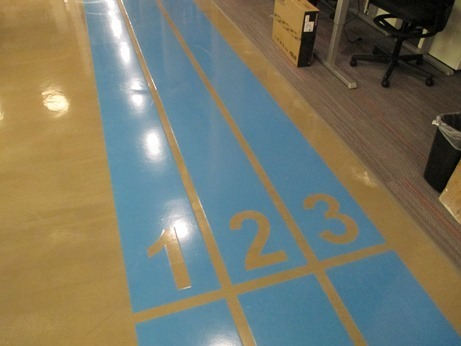 "A custom pigmented ""Hudl Blue"" DecoColor was rolled out using stencils designed to look like a racing track.  The system was finished with a second coat of DecoWear and a durable top coat of  satin urethane giving this floor a look as innovative and unconventional as the company that is Hudl."