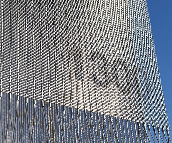 Helix 48 was used as the second screen behind each panel that created a continuous solar shading effect.  The contrasting metal fabrics help avoid a moiré pattern (an unwanted geometric shift in the pattern) from occurring for passing cars.