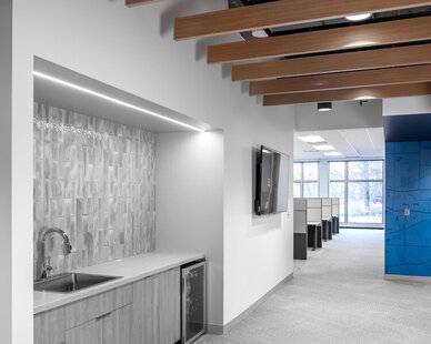 This corridor and walkway at the SRF Consulting Office features a small countertop space with a beautiful gray tile backsplash.   The wood ceiling beams add warmth to the office space and contrast beautifully with the neutral, gray carpet.