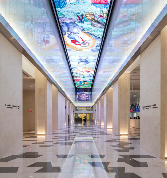 The shimmering white glass reflects images projected on the ceiling and conveys an icy appearance, symbolic of the original building's function as cold storage facility, circa 1923.   Photo by Alex Fradkin.