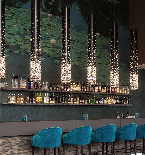 Beautiful lighting above this hotel bar by Swarovski Lighting