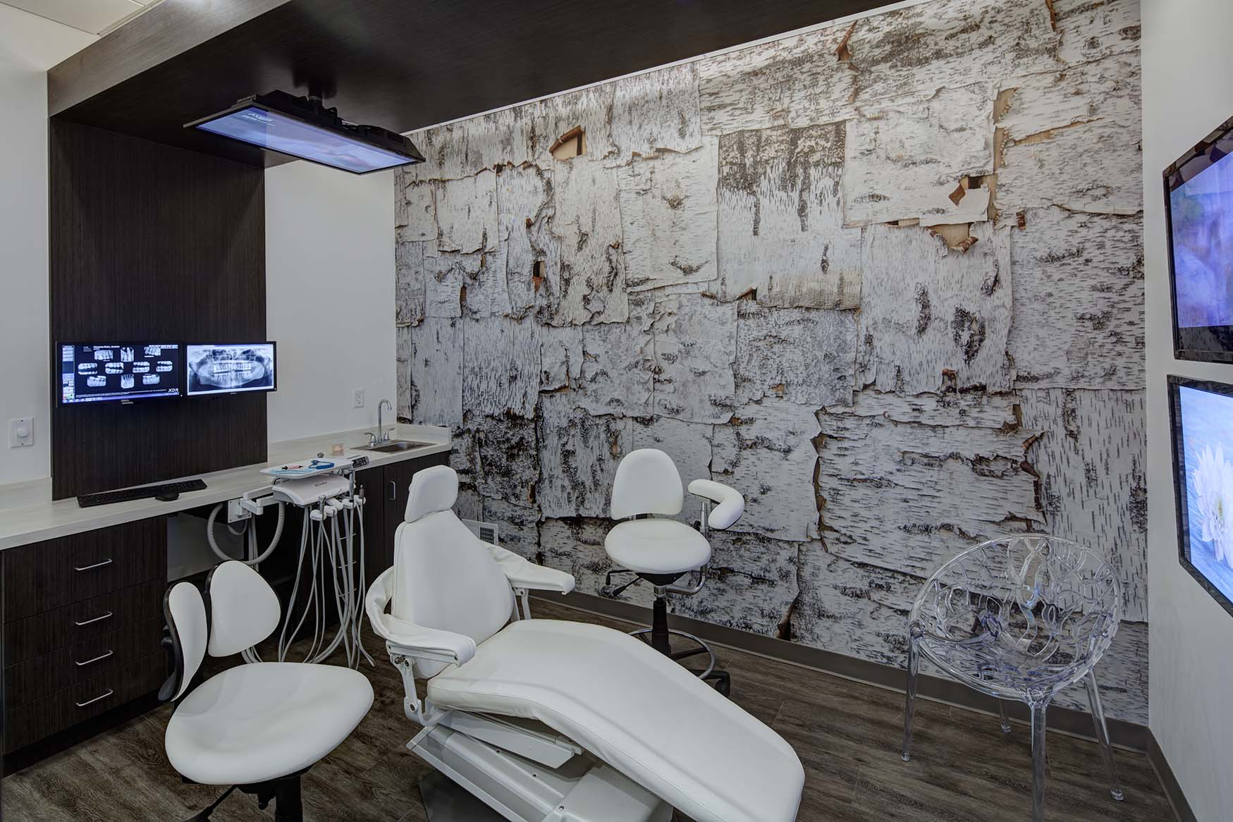 This birch wall mural creates a calm and comforting space in this dental office exam room.