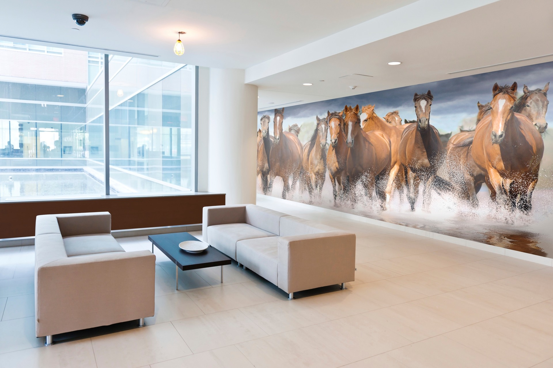 The Horses' Reflection wall mural by Murals Your Way is the perfect touch to this long hotel lobby wall.