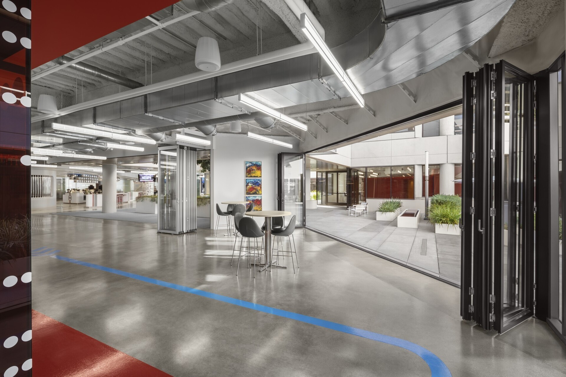 """To achieve a highly collaborative, highly flexible workspace, they gutted both floors. """"The biggest reason they took this space,"""" Mitchell elaborates, """"had to do with the indoor/outdoor possibilities."""" Those possibilities were maximized by eliminating most of the fixed glazing walls around the central courtyard on the ground floor, making it a contiguous part of the first floor, the light-filled, shining heart of the office. The space opens into to the second floor with 26 conference rooms of various sizes, and an endless selection of seating areas in which to work –couches, café tables, nooks, booths –all bathed in the glow of the central courtyard."""
