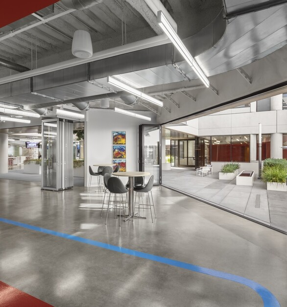 "To achieve a highly collaborative, highly flexible workspace, they gutted both floors. ""The biggest reason they took this space,"" Mitchell elaborates, ""had to do with the indoor/outdoor possibilities."" Those possibilities were maximized by eliminating most of the fixed glazing walls around the central courtyard on the ground floor, making it a contiguous part of the first floor, the light-filled, shining heart of the office. The space opens into to the second floor with 26 conference rooms of various sizes, and an endless selection of seating areas in which to work –couches, café tables, nooks, booths –all bathed in the glow of the central courtyard."