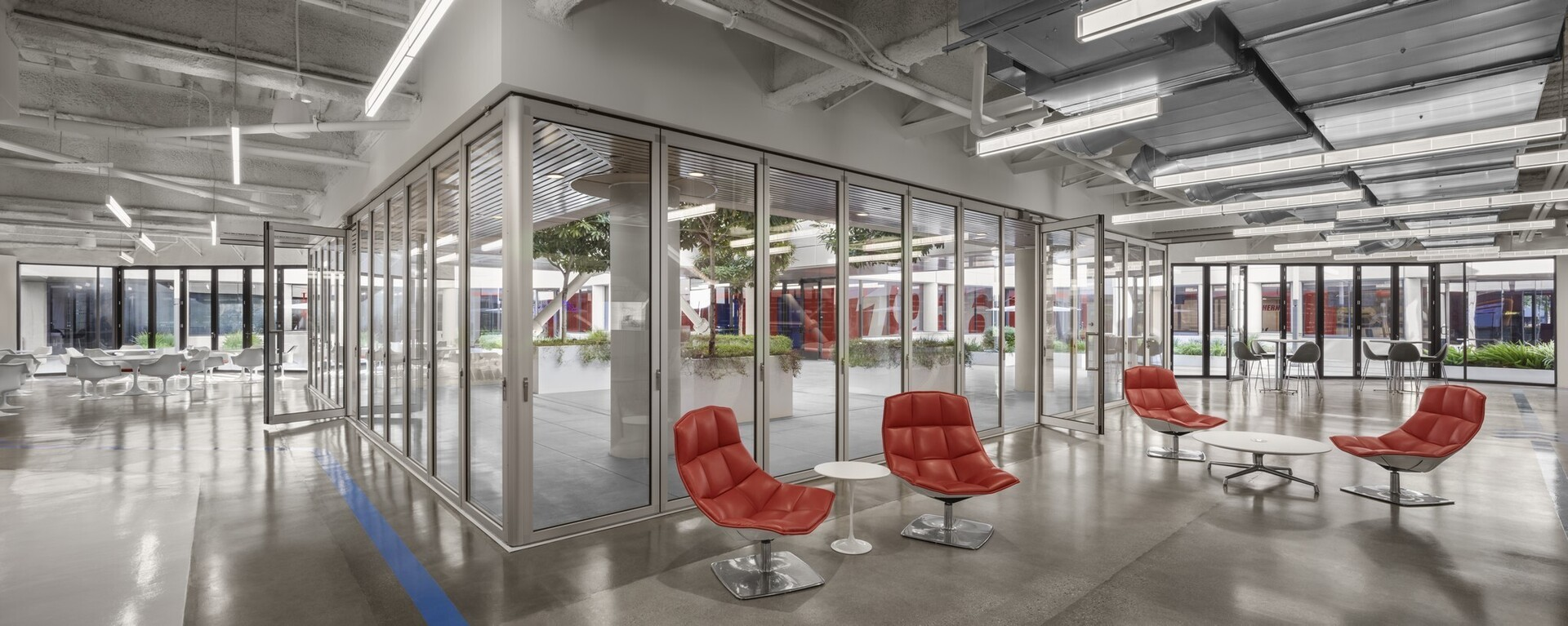 The moveable walls that make the open atrium practical are NanaWall opening glass wall systems. The longest is a single track sliding HSW60 system of 24 individual panels in two groups, over 80 feet in length. Two SL70 folding systems, 26 and 27 feet respectively, extend the atrium opening to more than 130 feet in all. The sliding panels go around corners, and three systems together account for about 75% of the area surrounding the atrium.