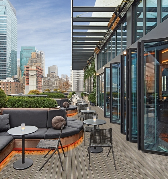 NanaWall SL70 Folding Glass Walls Castell Lounge Restaurant Exterior Rooftop Opened Modular Glass Walls and Guest Seating