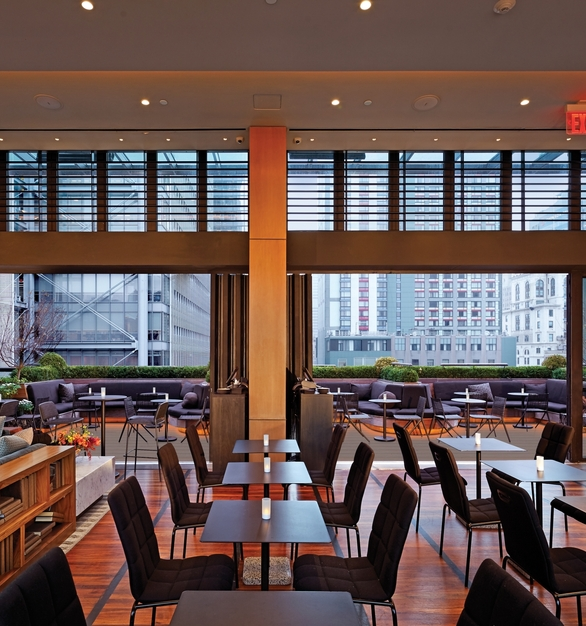 NanaWall SL70 Folding Glass Walls Castell Lounge Restaurant Interior Folded Modular Glass Walls and Guest Seating
