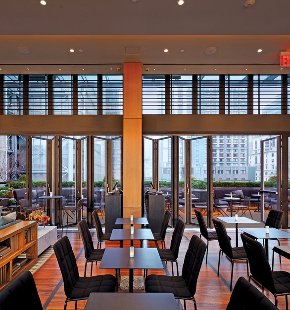 NanaWall SL70 Folding Glass Walls Castell Lounge Restaurant Interior Opened Modular Glass Walls and Guest Seating