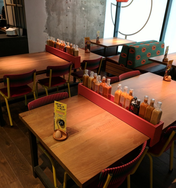 i2i Designs created these White Oak tabletops with a custom stain. They also created these fun sliding condiment trays for the tables.
