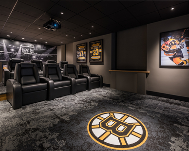 The new Bruins Den is complete with sound-proof walls, stepped reclining seating, a large projector and screen, and automated window treatments that will make guests feel like they are in a mini-movie theater. The room is complete with autographed Bruins memorabilia and custom wall graphics.  Photo Credit: Anton Grassl