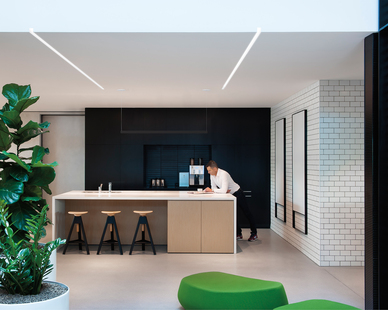 Office kitchen; office breakout area. Lighting: Notch 1 recessed linear luminaire by Fluxwerx. Trimless Dado endcap extrudes the hollow architecture to the edge of drywall soffit, delivering an actual slot in the ceiling.