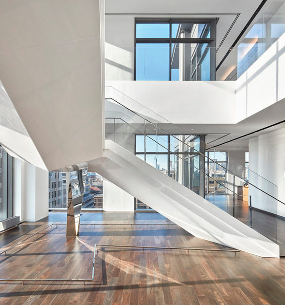 Spacious and luminous stairway at Cadillac's office headquarters in New York City, New York, featuring Walnut Steel Gray flooring by Nydree Flooring.