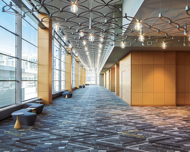 Filling the pre-function hallways on two floors are OCL's custom interlocking petal fixtures. This one-of-a-kind installation was created from over 2500 laser-cut metal petals and arrayed with hundreds of LED illuminated glass globes and downlights.