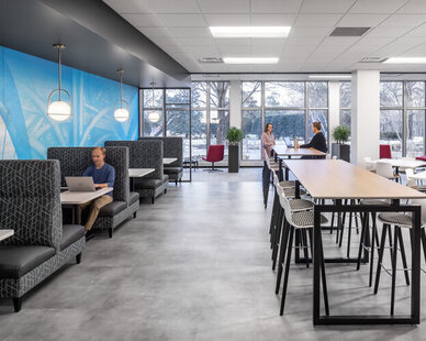 The commons space at SRF Consulting Group is illuminated with natural light from the large windows. There is ample space for small meetings and comfortable booth seating for all to enjoy.  The open office design is apparent in the lounge and break room space, along with the office areas.