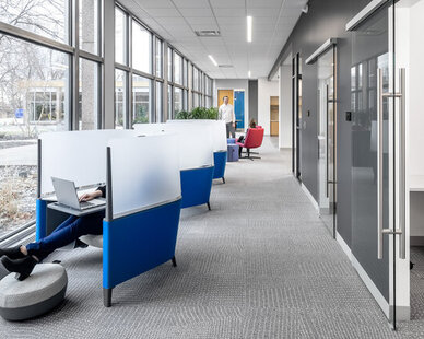 The unique blue chairs in this bright hallway offer privacy and comfort to employees at SRF Consulting.   The large windows illuminate the corridor and provide plenty of natural light for the meeting rooms as well.