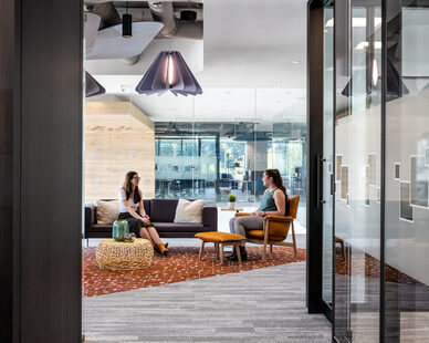 The Kwyet acoustic suspended pendant light provides sound absorption to this open office waiting area and lounge.
