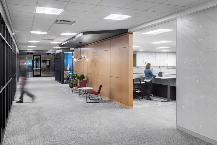 The entrance area and walkway in the office has a unique wooden partition wall along with the map mural designs on the surrounding walls.   There is a small waiting area with a modern light fixture, table and chairs. The open office design allows ample space for work and collaboration with others.