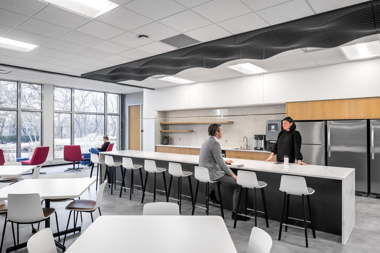 The lounge area and kitchen at SRF Consulting in Bismarck, ND feels open and modern with a white, marble countertop, high-top barstools, colorful lounge chairs and stainless steel appliances.