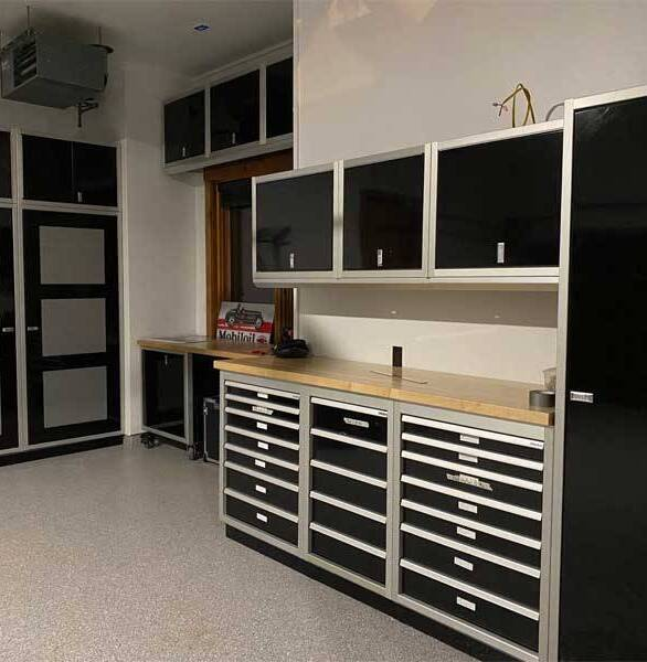 A residential garage with Moduline signature black PROII™ aluminum cabinets.  The drawered cabinets and overhead cabinets are a great addition.