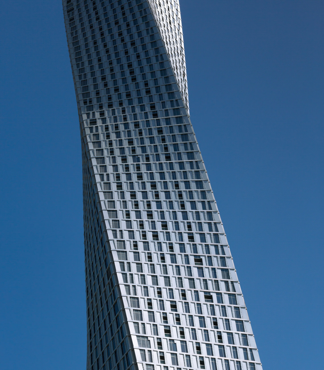 Cayan Tower is the world's tallest true twisting building. While the skyscraper's 73-floor plates are all identical, each is slightly rotated against the story below it, resulting in a full 90-degree twist over the course of the tower's 307-meter rise.  Images © SOM