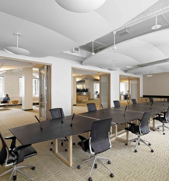 A long conference room table topped with PaperStone's most popular color–Slate. Slate pairs well with light colored woods for creating modern and unique furniture.