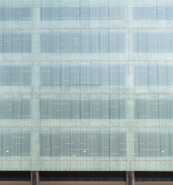 The pattern-fritted West glass facade appears to float over the concrete parking structure, held in the visually minimal clips. Photo by Kelly Drake Photography.
