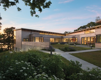 The modern neutral-toned library design and outdoor reading garden at the Eastham Public Library featuring Architect Series® Traditional windows and doors by Pella.