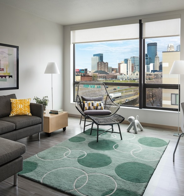 An apartment unit living room with a view of downtown Minneapolis at The Rose. The expansive windows come from the Pella® Impervia® line by Pella.
