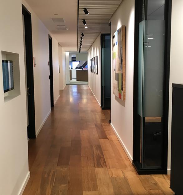 Reclaimed Teak wood flooring flows down this office hallway in Seattle, WA.