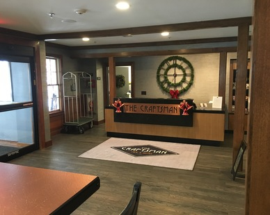 The inviting lobby + reception desk at Craftsman Inn and Suites featuring reclaimed wood with a custom charcoal finish, by Pioneer Millworks.