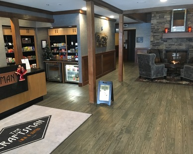 The inviting lobby at Craftsman Inn and Suites featuring reclaimed wood with a custom charcoal finish, by Pioneer Millworks.