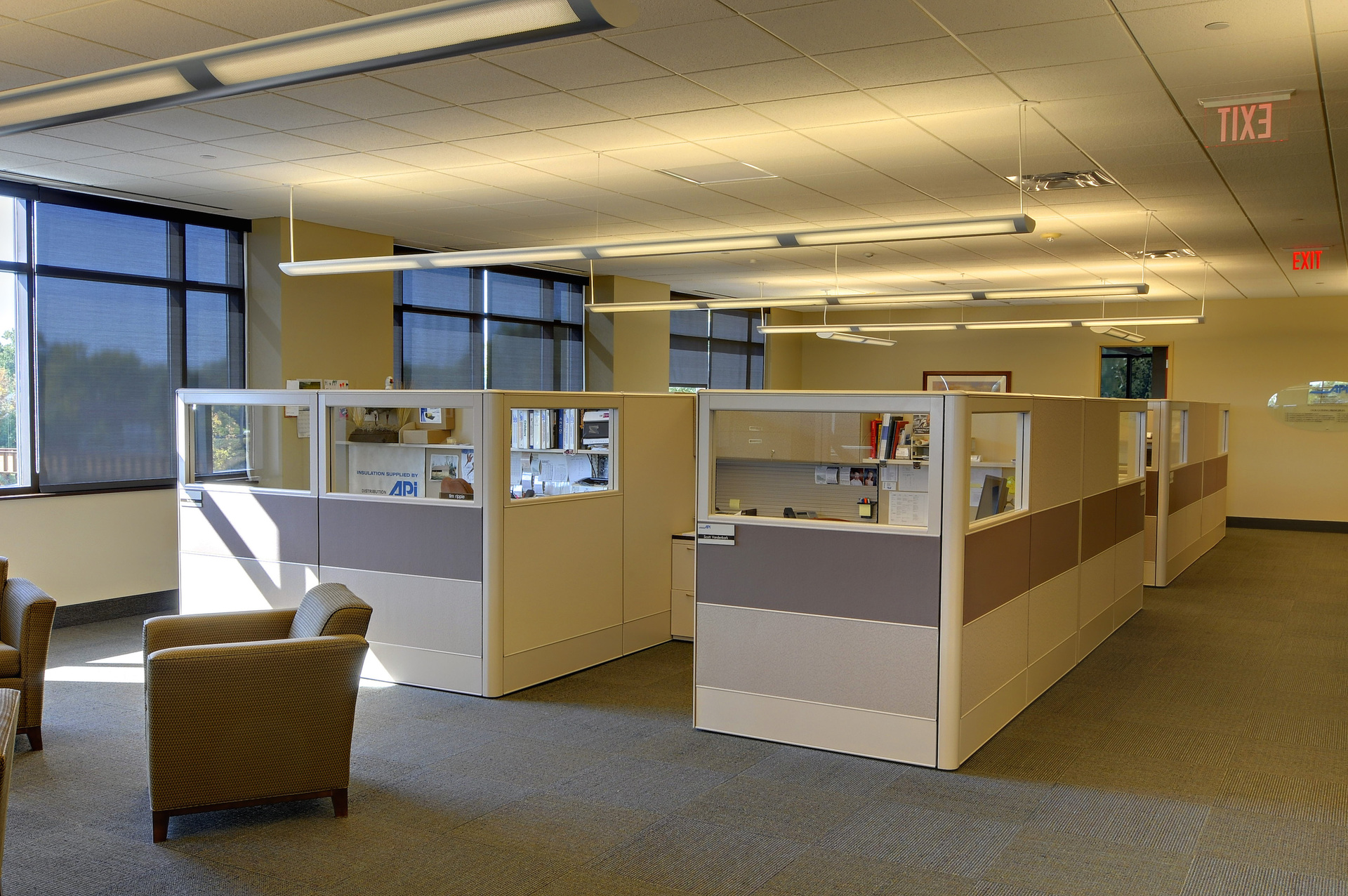 The open office space features linear pendant lights provided by Pulse Products.