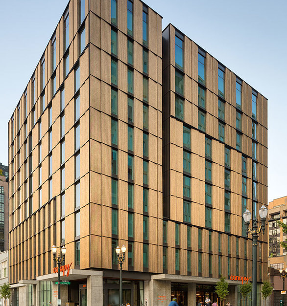 The modern exterior of the Canopy Hotel by Hilton in Portland, Oregon features custom-aged bronze corrugated aluminum panels by Pure + FreeForm.