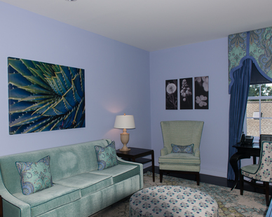 The peacock-colored sitting area in this hotel room is relaxing and quiet thanks to the sound-reducing drywall by QuietRock.